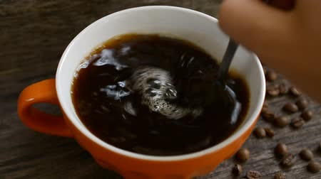 дополнение : Coffee cup close up hd slow motion footage with coffee beans on the table Стоковые видеозаписи