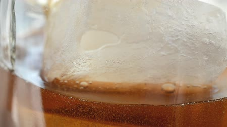 ice cube : Cola with Ice and bubbles in glass. Cola pouring. Stock Footage