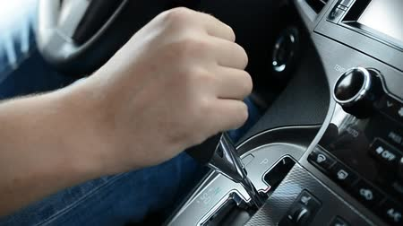 lever : Close-up of male hands switching automatic gearbox in expensive car, driver