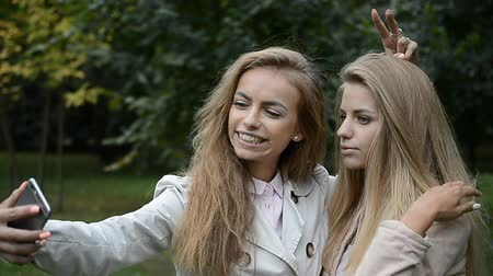 çekicilik : Two beautiful girls with long hair making selfie on the phone Stok Video