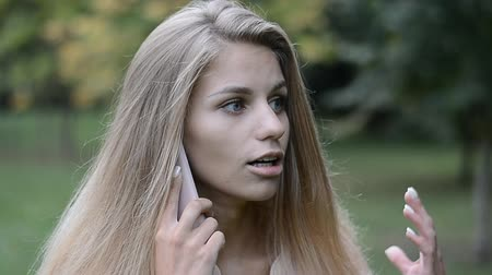 сплетни : portrait of a beautiful girl, blonde, talking on the phone Стоковые видеозаписи