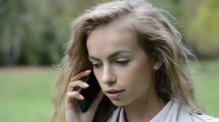 сплетни : Beautiful young girl using her cell phone, outdoor. Portrait of relaxed young lady in a summer park talking on phone