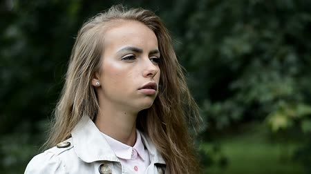addicted : Portrait of young woman smoking cigarette in city park Stock Footage