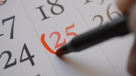 hónapokban : Signing a day on a calendar by red marker twenty fifth date