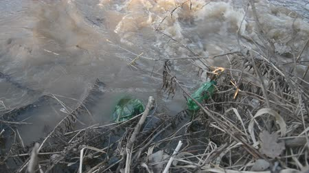 hijenik olmayan : two green plastic bottles in brown water, plastic recycling problems around the world. stock footage