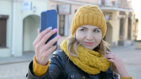 selfie girl : Young woman in a yellow knitted hat makes selfie photo HD stock footage Stock Footage