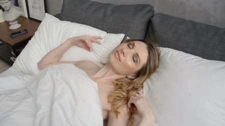 esfregar : Close up face of young Caucasian woman lying and stretching on bed after waking up early in the morning HD footage, blonde hair