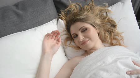 bekleyen : Attractive young Caucasian woman waking up in the early morning, then lying and stretching hd stock