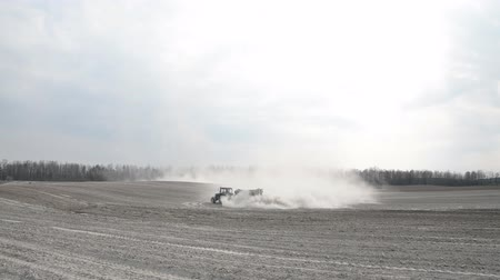 parasite : tractor Plows the land in the field. Spring field works hD Footage Stock Footage