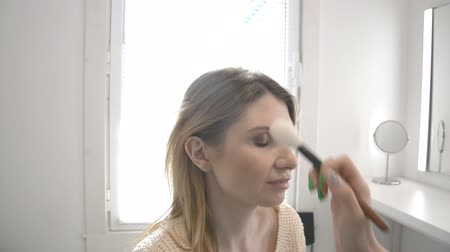 applying : Blonde make-up woman with eye-shadow and brush applys make-up. Beauty concept HD footage