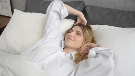 esneme : Beautiful blonde woman Slowly Waking up in the Morning hd stock footage