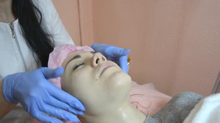 masaż twarzy : Cosmetologist cleansing patient skin in beauty clinic applying a cream mask Wideo