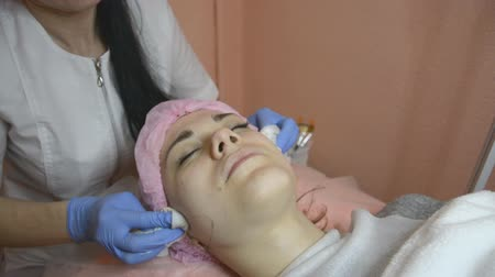 rubs : Cosmetologist rubs skin of face to female patient an intensive procedure Stock Footage