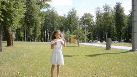 hůlky : two little children girl and girl playing outdoors and blowing soap bubbles
