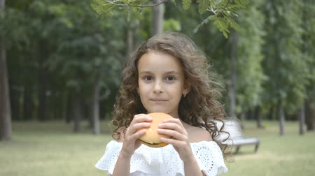 ハンバーガー : Close up of child face eating huge hamburger or cheeseburger with appetite in urban park