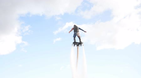 deli : Minsk, Belarus - September 14, 2019: Brave man in black balancing on flyboard, acrobatic performance at the bottom of the city in Minsk, Belarus Stok Video