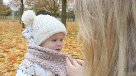 vestindo : mother care and love concept, mom wraps her little daughters scarf in autumn park hd stock footage