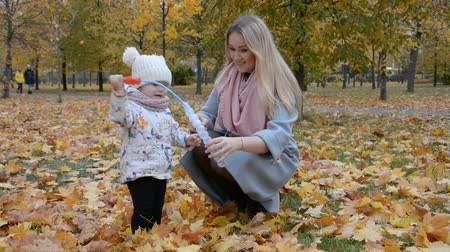 puericultura : Maternal love concept, mom and little daughter blow bubbles in autumn park hd stock footage
