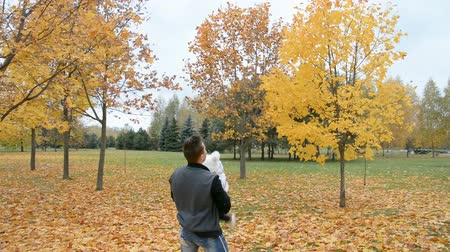 Dad throws up a happy little daughter outdoor, autumn city park