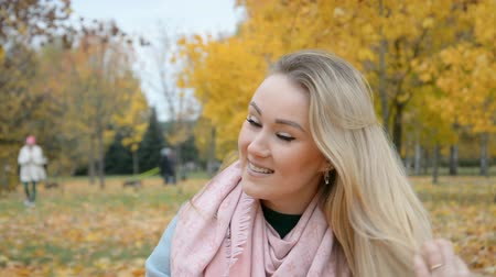 göğüs : Autumn outdoor Portrait of a beautiful young blonde woman smiling and looking at the camera, lifestyle concept