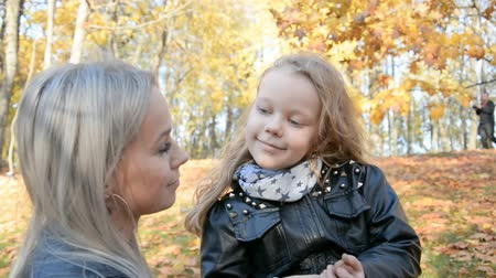 przytulanie : Maternal care concept, mom straightens hair to her little daughter in autumn park Wideo
