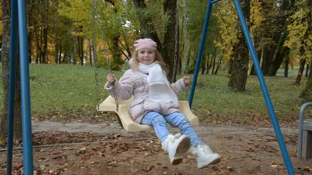 Little girl five years old playing with swings in the forest