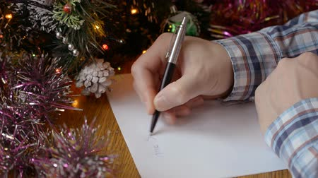 święta : man hands close-up at a table near a decorated Christmas tree and writes letter with wish a New Year letter to Santa Claus hd stock footage.