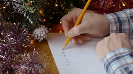 vragen : a man hands near a decorated Christmas tree and writes a New Year letter to Santa Claus close-up Stockvideo