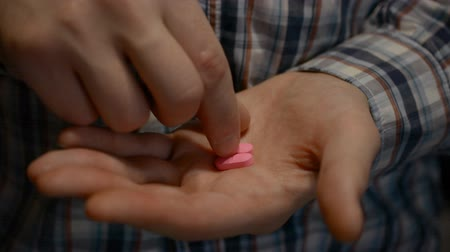 培養液 : Two pink antideprisant pills in a mans hand close, eating medicine concept