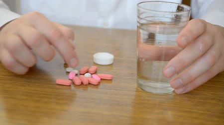 bağımlı : oung male businessman takes a pill at the workplace with water glasses close up