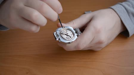 Watchmaker hands assembles a vintage watch close-up 影像素材