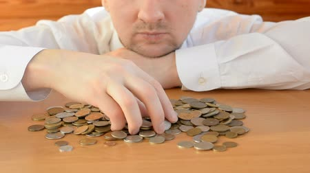 calcular : Portrait of bearded man sitting at the table in the kitchen counting money close-up