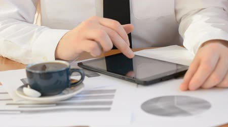 business and office concept - close up of business trader with graph on tablet pc screen and coffee in office hard working every day Wideo