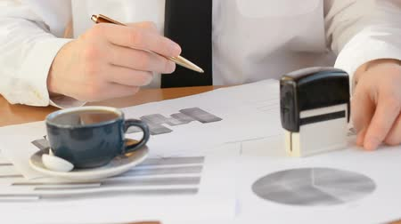 trader analyzes data from price growth charts for traded pairs in his office with a cup of hot coffee, economy concept
