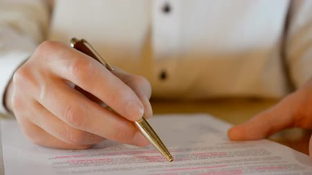Male hand with a gold pen read business contract, business concept 影像素材