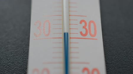 meteorologia : Blue scale on the thermometer on black background, temperature rises above 30 degrees Celsius, hot weather concept, climate change, warming