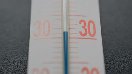 Blue scale on the thermometer on black background, temperature drops below 30 degrees Celsius, climate change concept