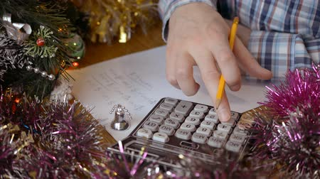 kalkulačka : male hands calculate the cost of buying Christmas fools close-up