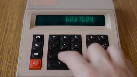 Old, retro or vintage calculator on table, made in USSR. Retro soviet calculator, Male hand pressing button, front view Stock Footage