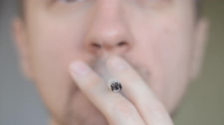 Close-up defocused man portrait with cigarette and fire lighter close-up Stock Footage