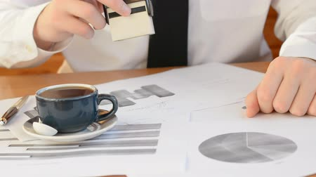 imposto : Printing on financial documents, a table of financial analytics and a cup of coffee