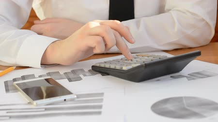 kalkulačka : Close up of a businessman hands working in calculator at office desk and analyzing graphs and charts Dostupné videozáznamy