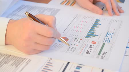 Close up of a businessman hands with pen working at office desk and analyzing graphs and charts, profit report checking, trading stock market concept Stock Footage