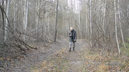 male traveler walking along a forest road with a phone in his hand, using satellite navigation to navigate the terrain