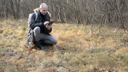 Male hiker with a tablet in his hands sits in the forest on the grass and tries to find the right direction for movement through the forest.