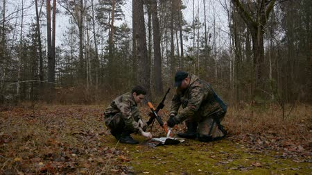 mapa : Two soldiers in the forest look at the map hd stock footage.