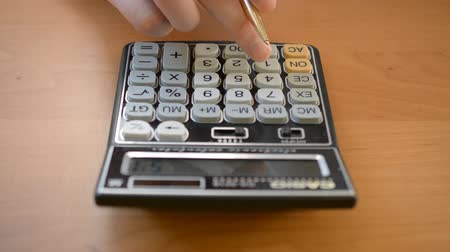Mens hands typing on calculator front view Stock Footage