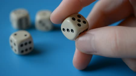morrer : Man fingers Holding game dice close-up hd stock footage, blue backround