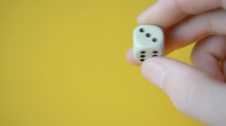 yirmi : dice in male fingers closeup on yellow background, left copyspace Stok Video