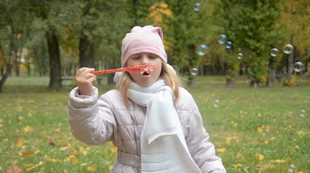 Portrait of funny lovely little girl blowing soap bubbles hd stock footage